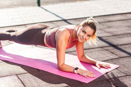 Motivated, happy athletic girl in tight pants training on mat outdoor summer day, doing plank exercise and smiling at camera, practicing aerobics, pilates workout. Pleasure from sport activity