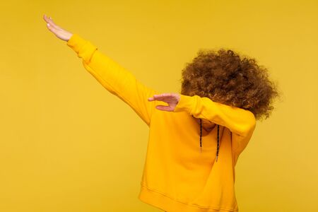 Portrait of curly-haired young woman in urban style hoodie hiding face with dab dance move, performing internet meme of success, dabbing trends. indoor studio shot isolated on yellow background