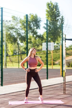 Positive fit athletic woman in tight pants warming up on mat outdoor summer day, doing aerobics or pilates exercise, workout routine, smiling feeling happiness and energy to practice sports activity Archivio Fotografico
