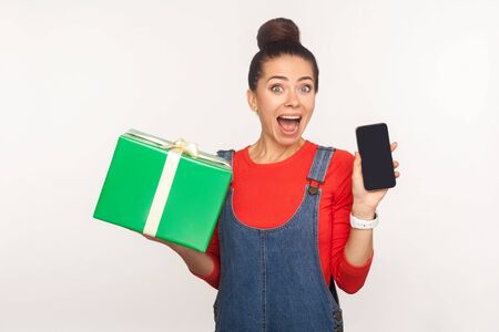 Wow, gift for mobile user! Portrait of amazed joyful pretty girl with hair bun in denim overalls holding present box and cell phone, shocked by holiday tariffs plan and bonus. studio shot, isolated