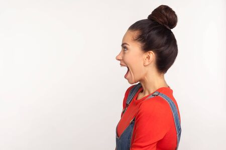 Side view of joyful surprised astonished pretty girl with hair bun looking impressed shocked by unbelievable news, shouting in amazement. indoor studio shot isolated on white background, copy space