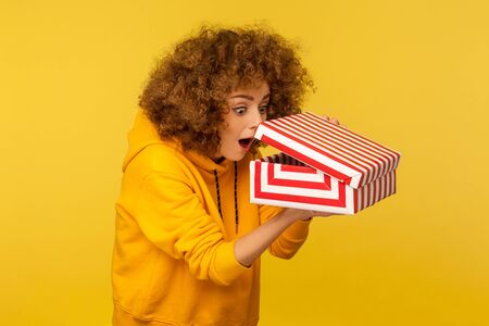 Portrait of funny, surprised, curious curly-haired woman in hoodie looking into gift box, unwrapping present and peeking inside with interest, open mouth in amazement. indoor studio shot isolated Stock Photo