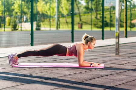 Full length, strong athletic woman in tight pants training on mat outdoor summer day, doing perfect plank exercise and looking motivated, practicing pilates workout. Health care, sports activity Archivio Fotografico
