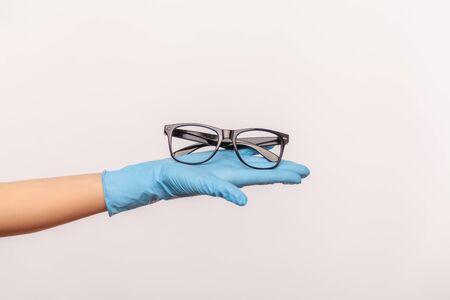 Profile side view closeup of human hand in blue surgical gloves holding and giving black eyeglasses frame. indoor, studio shot, isolated on gray background.