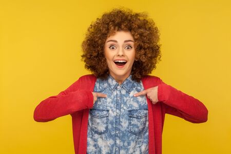 Wow, this is me! Portrait of amazed happy woman with curly hair pointing herself, looking surprised and boasting own success, proud of achievement. indoor studio shot isolated on yellow background