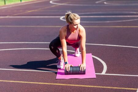 Motivated determined fit woman training on mat outdoor summer day, doing plank crunch abs exercise with foam roller, alternating knee workout. Warm-up before sports activity, health care concept
