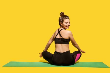 Back view cheerful woman with hair bun in tight sportswear sitting in lotus position on gym mat practicing yoga, turning head to camera and smiling joyfully, doing sports. Happy healthy lifestyle Stock Photo