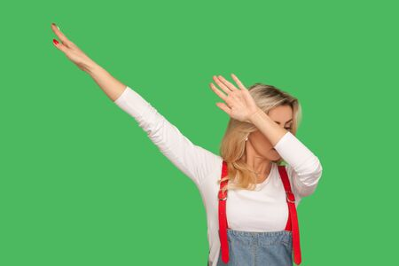 Portrait of woman in stylish denim overalls raising hands in dab dance pose, celebrating success, showing gesture of triumph, famous internet move. indoor studio shot isolated on green background