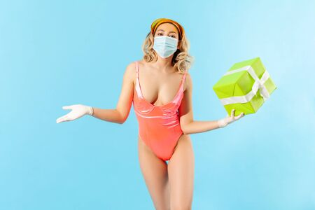 Woman in swimsuit and hygienic mask holding gift box, showing hand in surgical gloves, protective clothes to prevent coronavirus covid-19 infection. safe birthday celebration on quarantine. isolated