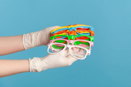 Profile side view closeup of human hand in white surgical gloves holding and showing many colorful different eyeglasses. indoor, studio shot, isolated on blue background.