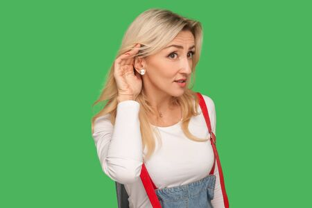 Portrait of nosy curious adult blond woman in stylish overalls keeping hand near ear listening carefully, concentrated at silent talk, trying to hear rumor. studio shot isolated on green background