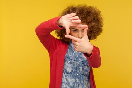 Portrait of woman with fluffy curly hair focusing eye at camera through photo frame gesture, cropping view, capturing moment, concentrating at target. indoor studio shot isolated on yellow background Stock Photo