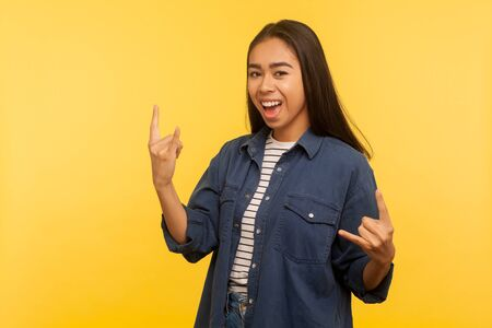 Portrait of joyful girl in denim shirt feeling crazy, showing devil horns, rock and roll hand gesture, delighted of success. indoor studio shot isolated on yellow background
