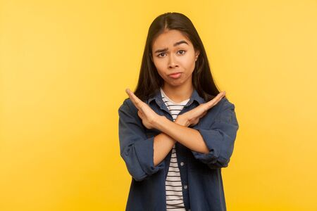 Portrait of dissatisfied girl in denim shirt gesturing stop, x sign with crossed hands, way prohibited, warning of troubles. indoor studio shot isolated on yellow background