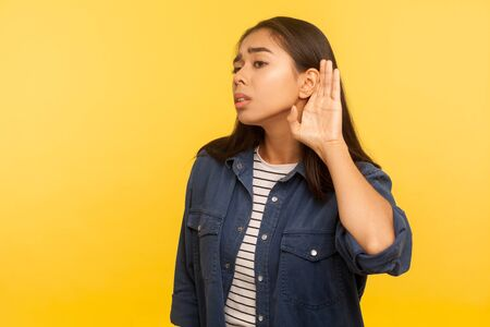 Portrait of girl in denim shirt holding hand near ear, listening attentively with interest private conversation, confidential talk. indoor studio shot isolated on yellow background