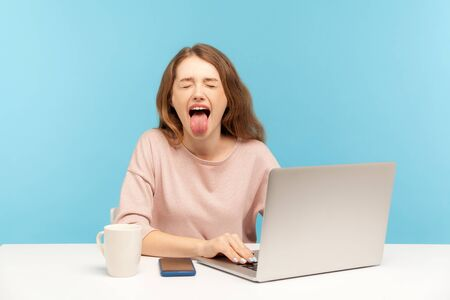 Naughty overworked businesswoman in casual clothes showing tongue out, expressing disgust and disobedience while working on laptop at home office. indoor studio shot isolated on blue background Imagens