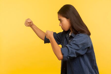 Let's fight! Side view of confident courageous girl in denim shirt keeping fists clenched, boxing and punching to side, struggle and self-defense concept. studio shot isolated on yellow background