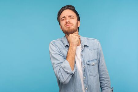 Portrait of flu-sick man in denim shirt clasping neck feeling unwell, suffering sore throat and inflamed tonsils, unbearable pain difficult to swallow. indoor studio shot isolated on blue background