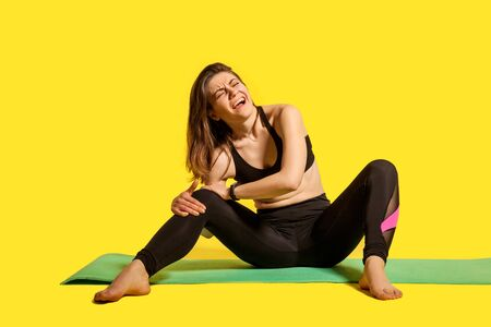 Sportswoman shouting from knee pain, sitting on gym mat, touching leg suffering joint injury after workout, muscle strain, hurting to move sprained ligaments. studio shot isolated on yellow background