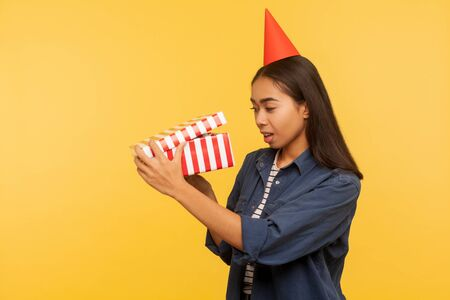 Portrait of curious happy brunette girl in denim shirt and funny cone hat opening birthday gift, looking inside with interest, unpacking present on party celebration. indoor studio shoot isolated Imagens