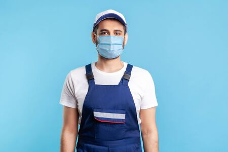 Portrait of handyman in overalls, mack and cap looking to camera, profession of service industry, courier delivery. Expert house repairman in workwear smiling. indoor shot isolated on blue background