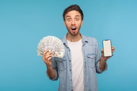 Portrait of surprised man in worker denim shirt holding dollar banknotes, cell phone and looking at camera with naive amazed expression, shocked by online betting win. indoor studio shot isolated