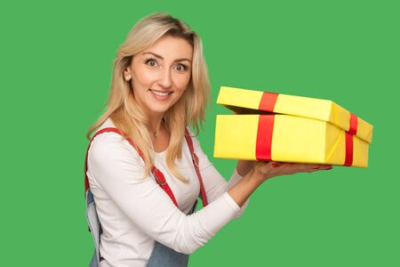 Portrait of positive pleased adult woman in denim overalls holding unwrapped gift, unpacking present and looking with toothy smile, joyful satisfied expression. indoor studio shot, green background