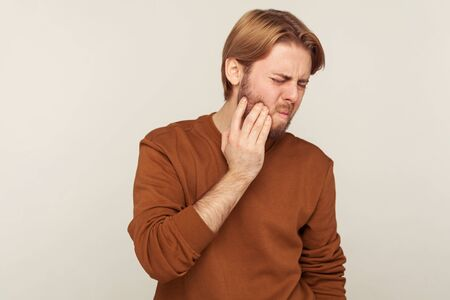 Portrait of bearded man in sweatshirt holding sore cheek, frowning from acute tooth pain, suffering periodontal disease, cavities. studio shot isolated on gray background
