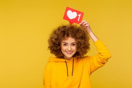 Internet blogging. Portrait of happy smiling curly-haired young woman in urban style hoodie holding heart like icon over head, social media button. indoor studio shot isolated on yellow background