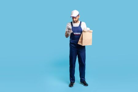 Full length responsible expert courier in blue uniform holding groceries bag and chatting with client on cell phone, reading message, using mobile app to accept online order. studio shot isolated