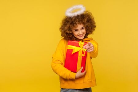 Hey you, happy holidays! Portrait of cheerful curly-haired angelic woman with saint nimbus pointing to camera and holding wrapped christmas gift box. indoor studio shot isolated on yellow background