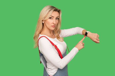 It's late, time to go! Portrait of bossy strict adult woman in stylish overalls pointing at wrist watch and looking with displeased impatient expression. studio shot isolated on green background