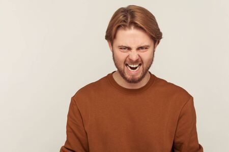 Portrait of annoyed aggressive bearded man in sweatshirt roaring wild to camera, expressing strong anger irritation, screaming crazy and full of hate . indoor studio shot isolated on gray background