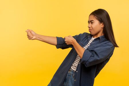 Portrait of diligent purposeful girl in denim shirt pulling invisible heavy burden, striving hard to achieve success, dragging with persistence. indoor studio shot isolated on yellow background