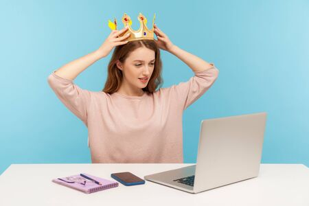 I am best queen. Arrogant self-confident ambitious businesswoman putting crown on head and looking at laptop screen, sitting in her office workplace. indoor studio shot isolated on blue background