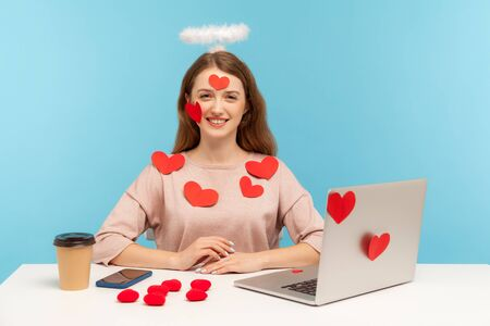 Angelic friendly woman with kind smile sitting at workplace office, all covered with sticker love hearts, full of valentine's day greetings, romance. indoor studio shot isolated on blue background