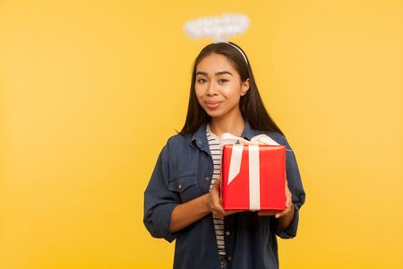 Holiday present! Portrait of lovely angelic girl with holy nimbus holding her birthday gift and smiling pleased to camera, looking satisfied and happy. indoor studio shot isolated on yellow background Archivio Fotografico