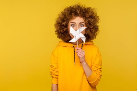Origami pinwheel toy on stick. Portrait of curly-haired woman in urban style hoodie peeking out behind paper windmill and looking with amazed big eyes. indoor studio shot isolated on yellow background