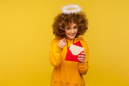 Love message. Portrait of pretty curly-haired angelic woman with saint nimbus holding letter envelope and pointing to camera, smiling playfully. indoor studio shot isolated on yellow background