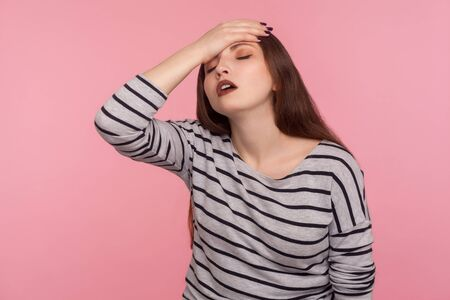 Facepalm. Portrait of upset woman in striped sweatshirt holding hand on forehead, blaming herself for forgotten event, bad memory, feeling sorrow and shame. studio shot isolated on pink background