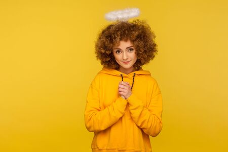 Portrait of kind lovely curly-haired hipster woman with saint nimbus holding hands in prayer and looking at camera with obedient modest expression. indoor studio shot isolated on yellow background