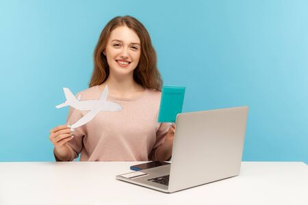 Friendly woman, travel agent holding passport and paper airplane, looking at camera with toothy smile, advertising hot tours with airline transportation. indoor studio shot isolated on blue background