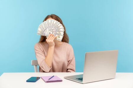 Money making advertisement. Woman employee sitting at workplace and covering her face with dollar banknotes, showing big salary, business profit, income. indoor studio shot isolated, blue background Stock Photo