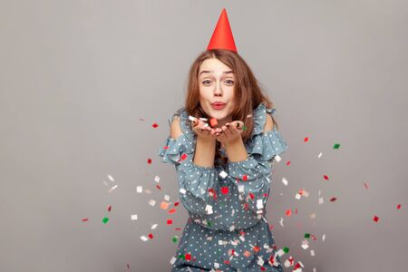 Carefree happy girl in ruffle blouse and funny party hat blowing glitter, smiling enjoying birthday, celebrating success, holiday event, festive mood. indoor studio shot isolated on gray background