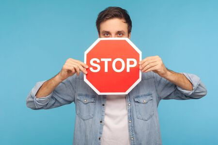Way prohibited! Portrait of man in worker denim shirt peeking out of Stop road traffic sign, showing symbol of restrictions and forbidden access. indoor studio shot isolated on blue background Standard-Bild