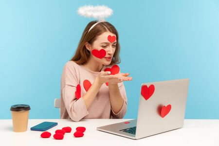 Beautiful angelic woman with kind expression sitting covered with sticker hearts, sending romantic sensual air kiss to laptop screen, dating on video call with lover. indoor studio shot, isolated