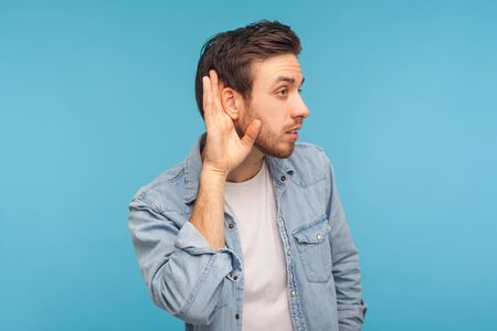 What? I can't hear! Portrait of man in worker denim shirt holding hand near ear and listening carefully, having hearing problems, deafness and misunderstanding in communication. studio shot isolated