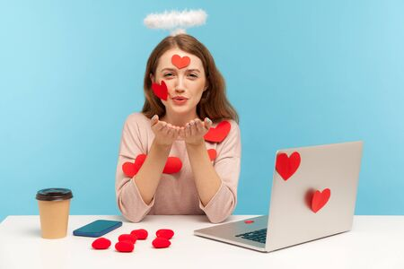 Angelic woman with kind expression sitting at workplace office, all covered with sticker love hearts, sending romantic sensual air kiss, full of valentine's day greetings. indoor studio shot, isolated