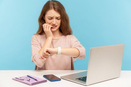 Too late, no time to meet deadline! Upset worried woman employee sitting at workplace and looking at wrist watch with anxiety, nervous about late hour. indoor studio shot isolated on blue background