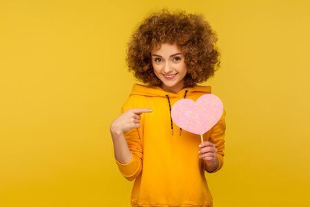 Romantic feelings. Portrait of charming curly-haired woman in urban style hoodie pointing at pink heart and smiling, symbol of care, love, kindness. indoor studio shot isolated on yellow background